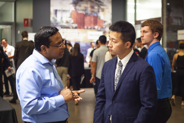 A potential employer speaks with a student at a career fair