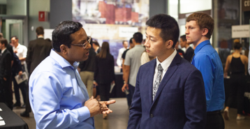 An employer talking with a student at a career fair