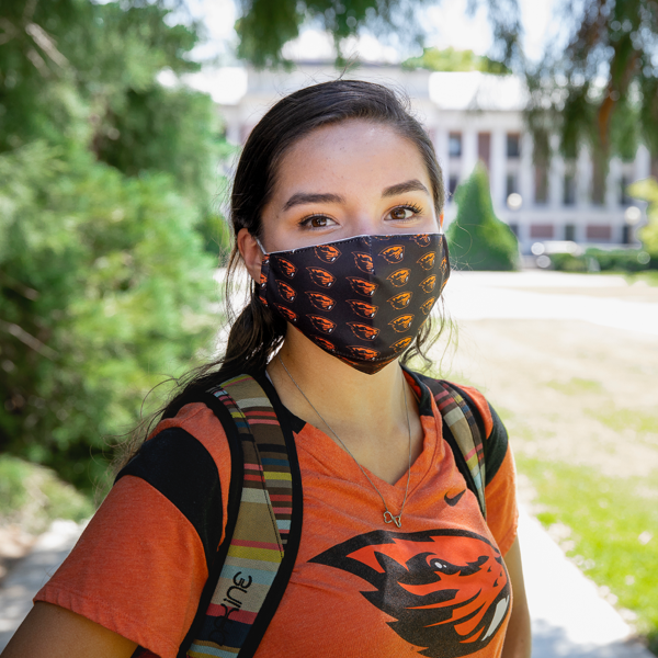 An OSU student standing outside in a mask