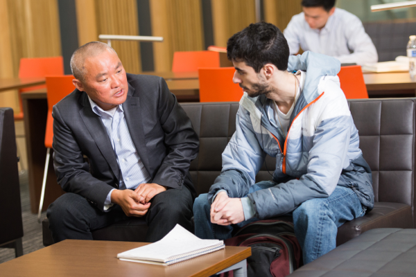 A College of Business faculty member meets with a student in Austin Hall